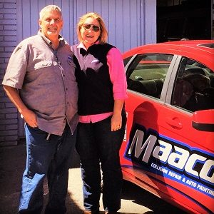 Woman and man standing next to Maaco branded car posing.